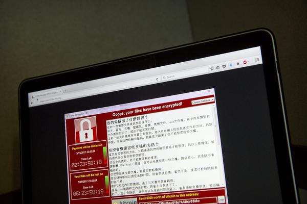 In this May 13, 2017 file photo, a screenshot of the warning screen from a purported ransomware attack, as captured by a computer user in Taiwan, is seen on laptop in Beijing. (Mark Schiefelbein/AP)