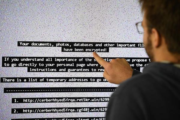 "An IT researchers shows on a giant screen a computer infected by ransomware in 2016.Paradise where computer viruses blossom under the watchful eye of scientists, the Laboratory of high security (LHS-PEC) of Rennes is a small fortress from where emerge the first studies on the ""ransomwares"", those digital brigands which Dominate the malware market. / AFP PHOTO / DAMIEN MEYER        (Photo credit should read DAMIEN MEYER/AFP/Getty Images)"