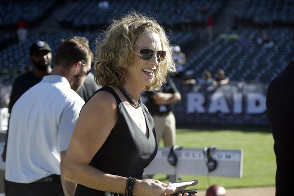 Announcer Beth Mowins walks on the field before a 2015 NFL preseason football game between the Oakland Raiders and the St. Louis Rams in Oakland, Calif.