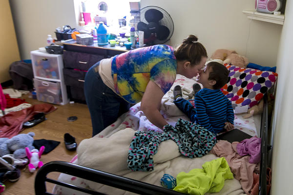 Rosa Benitez kisses her 2-year-old son Brandon after checking on him while he was in his room playing. (Jesse Costa/WBUR)