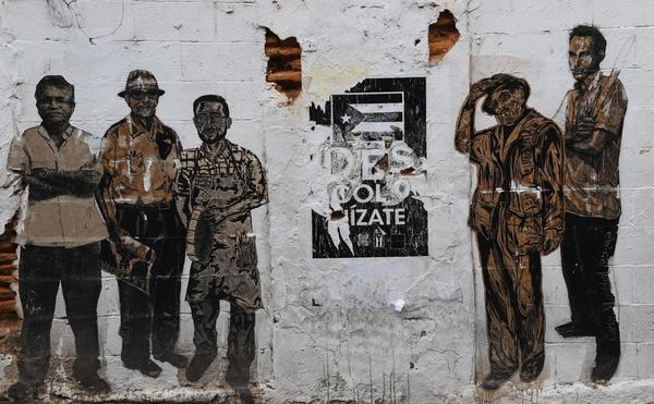 A mural displays notable historical figures and a fading Puerto Rican flag on a dilapidated building in San Juan earlier this month. Between its public-sector debt and money owed pension funds, the U.S. territory is grappling with more than $120 billion in debt.