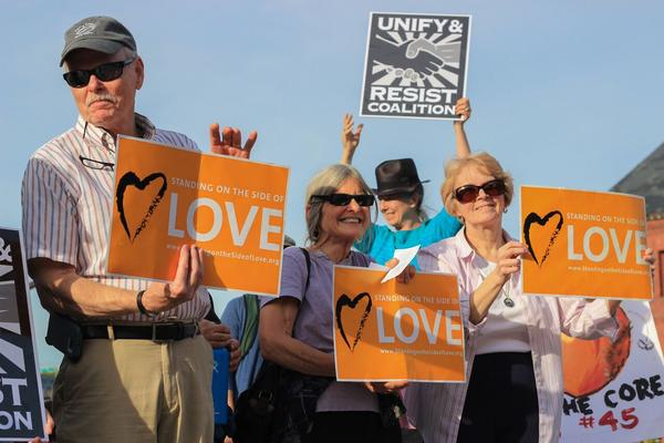Demonstrators hold signs from the Unitarian Universalist Association's social justice campaign, Standing on the Side of Love.