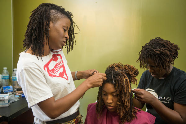 Tameka Stigers, left, and Ivy Perry, right, braid LaQuinn Laws' hair in June 2015 in St. Louis.