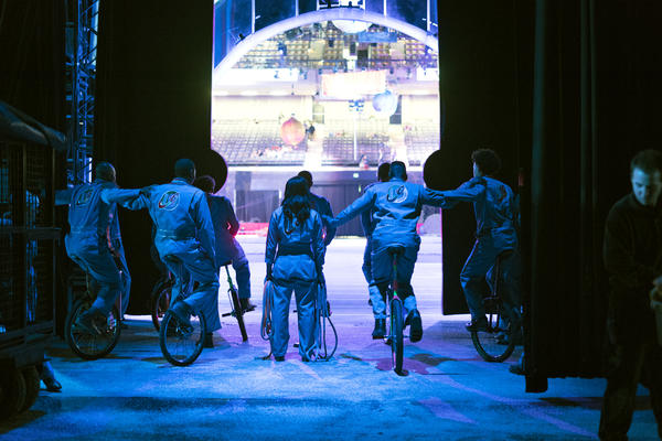 A team of unicyclists hold on to each other backstage. The King Charles Troupe has been playing basketball on unicycles since the '60s.