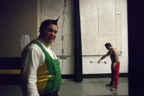 Clowns and trapeze artists loosen up backstage before the show.
