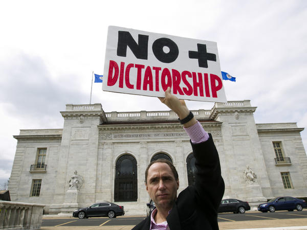 A protester demonstrates against the Venezuelan government outside the Organization of American States during a special meeting in April. The Trump administration has imposed economic sanctions on members of the country's Supreme Court.