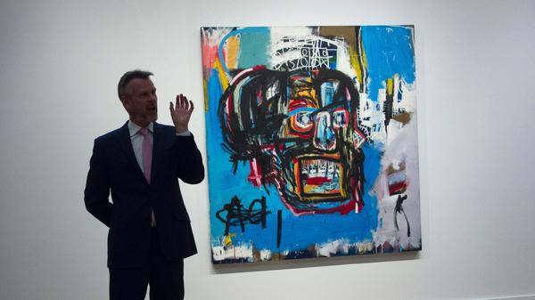 Jean-Michel Basquiat's untitled painting of a skull is displayed behind an official with Sotheby's, which offered the media a preview earlier this month. On Thursday, the work sold for $110.5 million — the highest sum ever paid at auction for a work by a U.S. artist.