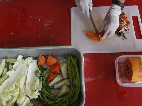 """Unce Fat"" is on a diet. Veterinarian Supakan Kaewchot prepares a healthy meal for the obese macaque at a rehabilitation center Bangkok, Thailand, Friday."