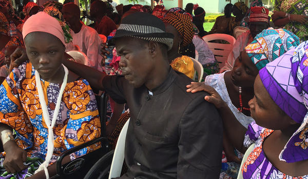 Amina Bulama, one of the freed girls, is in a wheelchair with her left arm in a sling. The cause of her injuries is not known. Her father, Bulama Jona, believes that forgiving Boko Haram is the best way for families to overcome the trauma. Esther Bulama Jona, his wife and Amina's mother, is seated at right.