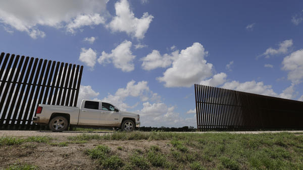 A farmer passes along a border fence that divides his property in Mission, Texas. The state alone shares more than 1,200 miles of border with Mexico.