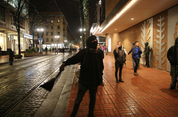 <p>A young protester was stopped by others in downtown Portland as he attempted to grab a ladder from a nearby construction site on Jan. 20, 2017.</p>