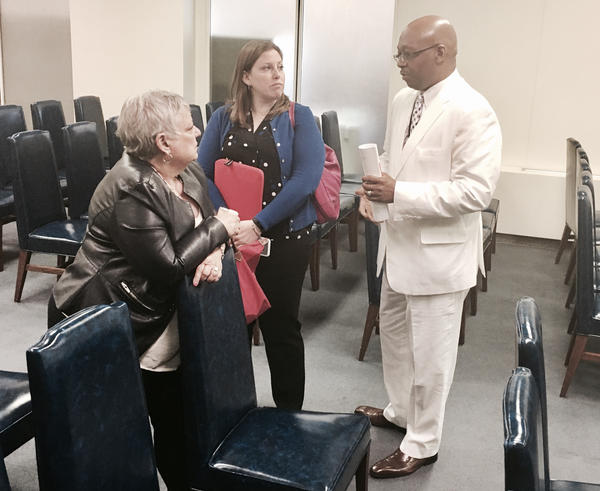"""Rep. Will Davis (D-Homewood) chats with advocates representing suburban school districts Wednesday. (In observance of the annual """"seersucker caucus"""" day at the capitol, he's wearing a white-on-white seersucker suit.)"""