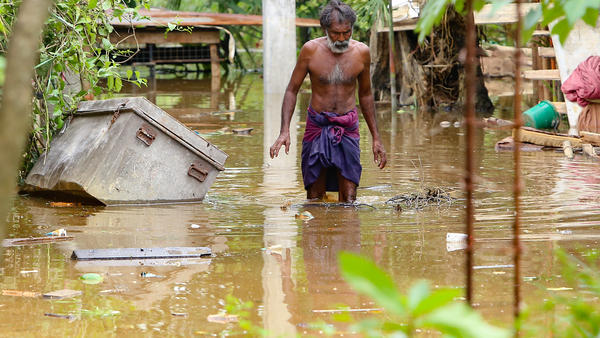 A Sri Lankan man walks through floodwaters in Kaduwela, Sri Lanka, on Friday. More than 90 people were reported dead after unusually heavy rains triggered floods and mudslides in Sri Lanka.
