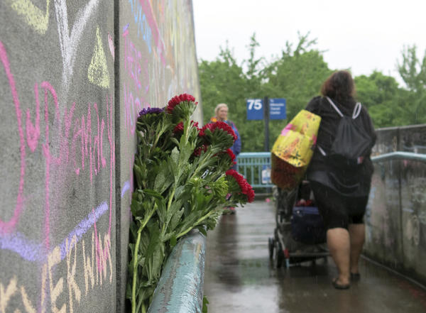 Commuters walk past a rain-soaked memorial on Tuesday to two men who were fatally stabbed after trying to stop another man who went on an anti-Muslim tirade against two young women in Portland, Ore.