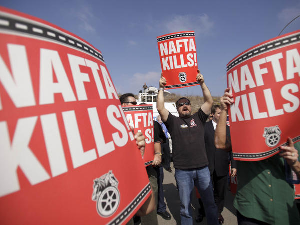 "<p>Teamsters union members hold signs that read, ""NAFTA kills,"" during a news conference by congressmen and union leaders against the cross-border trucking program Oct. 19 in San Diego.</p>"