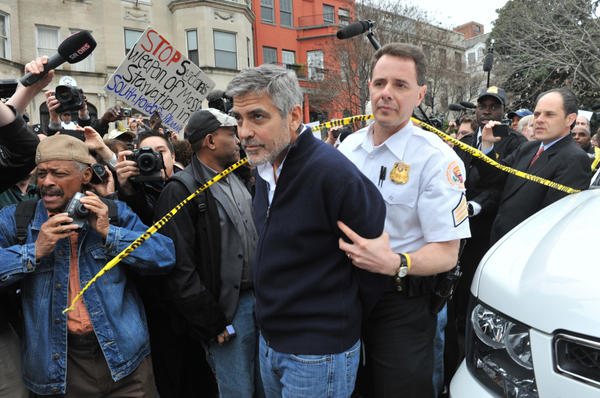 Actor George Clooney is led away in handcuffs from Sudan's embassy in Washington, D.C., on Friday. Clooney, his father, Nick, and others including Democratic Rep. Jim Moran of Virginia and NAACP President Ben Jealous, were arrested as they demonstrated to bring attention to the humanitarian crisis in Sudan.