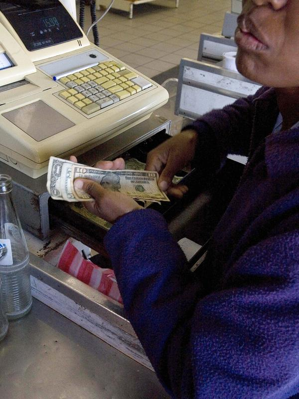 Zimbabwe now uses the U.S. dollar as its main currency, though the bills are often extremely dirty and falling apart due to constant use. Here a cashier holds U.S. dollars in good condition at a supermarket in the capital Harare in 2009.