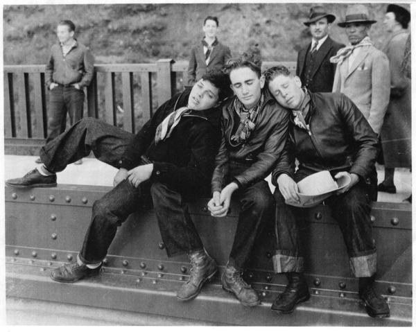 Edgar Stone (left), Marshall Weigel and Stuart Greenberg were exhausted after walking across the Golden Gate Bridge on the day it first opened. A photographer snapped them for this image, which appeared in <em>The San Francisco News-Call Bulletin</em>.