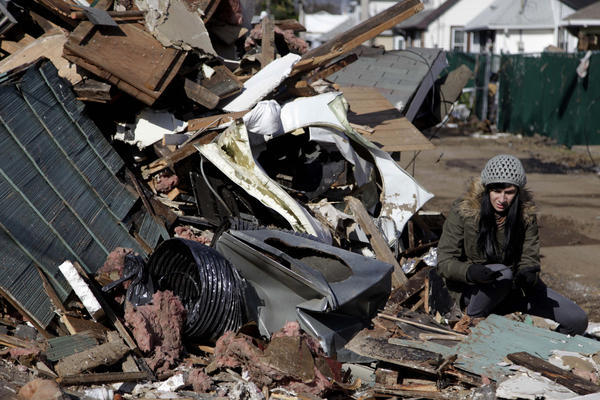 Julie Traina tries to recover some personal items from her parents' destroyed home.