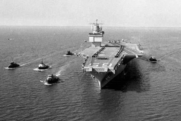 The world's largest ship, the nuclear-powered aircraft carrier USS Enterprise, is shown leaving Newport News, Va., with a five-tugboat escort during initial sea trials in 1961.