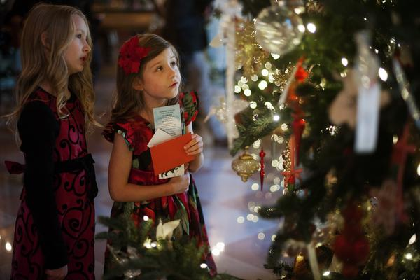 "Lauren Rae (left) and Olivia Marlow look at the ornaments in the Grand Foyer during the first viewing of the White House 2012 holiday decorations in Washington, D.C., on Wednesday. This year's theme is ""Joy to All."""