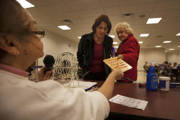 Bingo caller Zinnia Rosado of St. Cloud, Fla., checks a winning bingo card at the Robert Guevara Community Center.