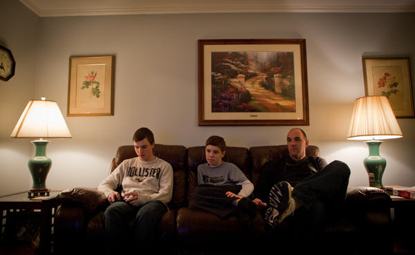 Brian Jordan checks his iPhone while Kevin and their father watch television.