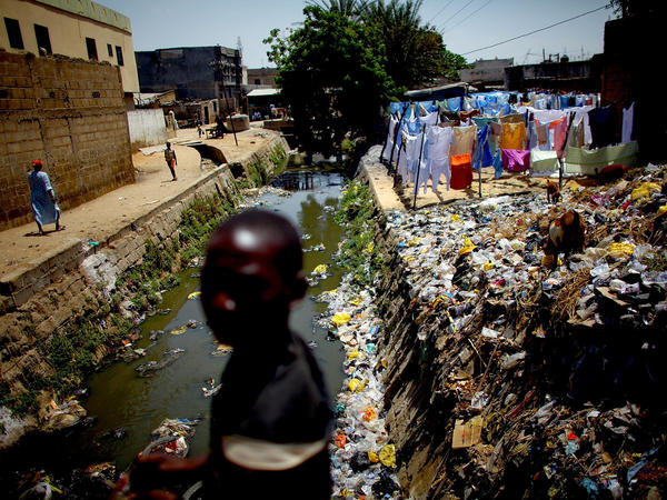 A child crosses a bridge over the cement-lined Gogo stream, which flows behind the main market in Kano, Nigeria. Sanitation workers regularly test the sewage here for the presence of the polio virus.
