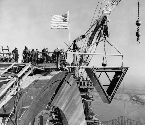 Workmen bring the keystone section into place on Oct. 28, 1965. The crane in the background lifted the 10-ton stainless steel section. The Mississippi River is to the right.