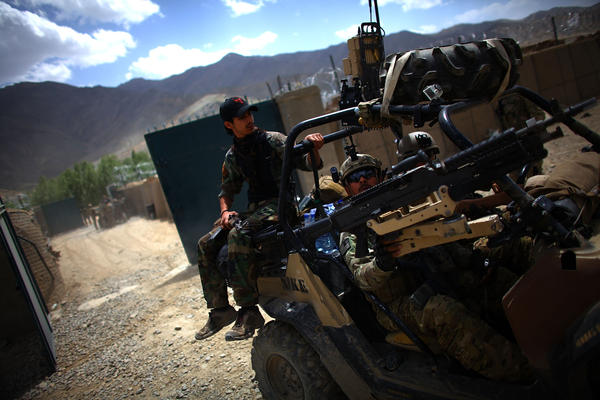 An Afghan National Army Special Forces soldier rides on the back of a Green Beret vehicle near the village of Kasan, in Wardak province. As American forces are drawing down in Afghanistan, they are increasingly relying on Afghan forces to take the lead, especially more elite forces like the ANASF who are trained by U.S. Army Special Forces.