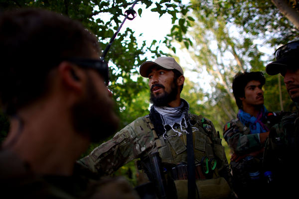 Capt. Nasir (center) talks with members of Green Berets before a shura in Kasan. The mission of the Green Berets and ANASF is to recruit more Afghan local police to act as an armed neighborhood watch that will serve as the first line of defense against the Taliban.