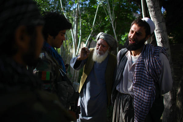 Afghan National Army soldiers search a group of men near Kasan while local elders and local police hold a shura to discuss security.