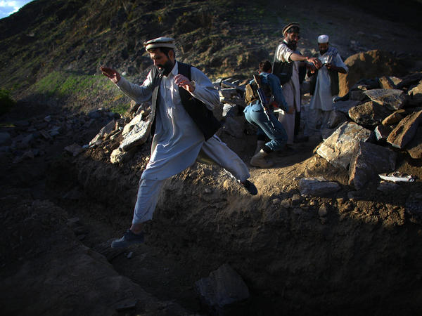 Afghan National Army soldiers search a group of men near the village of Kasan.