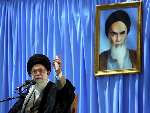 Supreme Leader Ayatollah Ali Khamenei delivers a speech in a ceremony marking the anniversary of the death of the late revolutionary founder Ayatollah Ruhollah Khomeini, shown in the picture in background, at his shrine just outside Tehran, Iran on June 4.