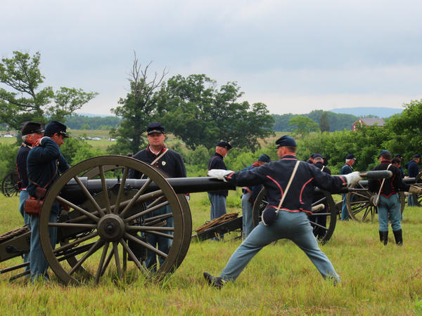 Union re-enactors prime cannons with black powder for a demonstration of artillery fire as part of the Gettysburg National Military Park's commemoration.