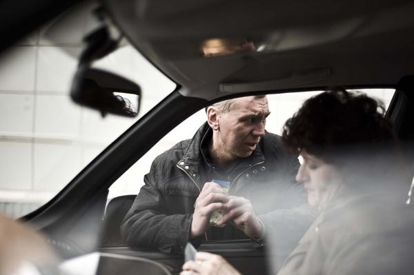 Sputnik nurse Marina Bogdanova gives medications to Sergei Gaptenko, who is close to finishing treatment for drug-resistant tuberculosis. Sometimes Gaptenko isn't at home when the nurses come to give him his daily medications, so the team has to drive around Tomsk looking for him.