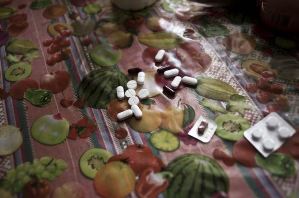 Kharkov takes a handful of pills each day to stop his tuberculosis infection. Treatment for drug-resistant TB can last two to three years.