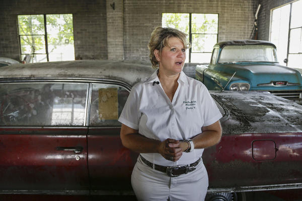 Auctioneer Yvette VanDerBrink in front of a 1963 Chevrolet Impala and a 1958 Cameo pickup truck at the Lambrecht Chevrolet car dealership.