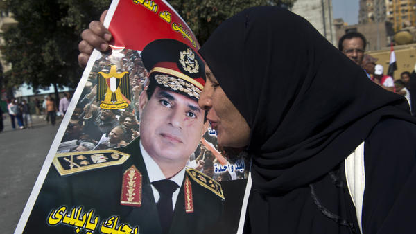 An Egyptian woman kisses a poster of Gen. Abdel-Fattah el-Sissi as she arrives at Cairo's Tahrir Square to mark the 40th anniversary of the 1973 Arab-Israeli war last month. Many are calling for the general to run for president next year, but so far he has remained coy.