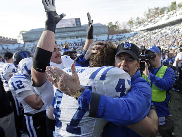 Duke coach David Cutcliffe hugs linebacker David Helton following Duke's 27-25 win over North Carolina on Nov. 30.