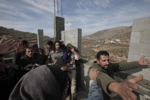 Palestinians (front and left) try to prevent fellow Palestinians from the village of Qusra from attacking a group of Israeli settlers after they sparked clashes upon entering the village near Nablus, in the Israeli-occupied West Bank, on Jan. 7.