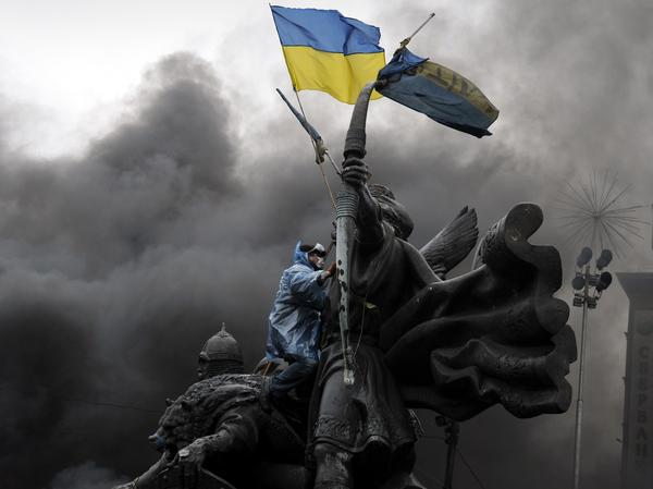 An anti-government protester sits on the Founders of Kiev monument during clashes with riot police in central Kiev.