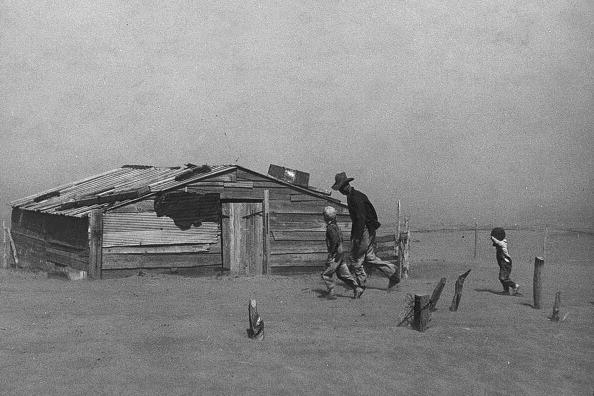 "Father and sons walk through a dust storm in Cimarron County, Okla. (1936). Steinbeck writes: ""The dust was evenly mixed with the air, an emulsion of dust and air. Houses were shut tight, and cloth wedged around doors and windows, but the dust came in so thinly that it could not be seen in the air, and it settled like pollen on the chairs and tables, on the dishes."""
