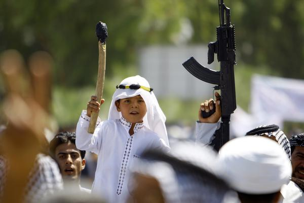 An Iraqi boy, carrying a stick amid men wielding guns, joins a demonstration in Najaf on June 14. The Shiite demonstrators were showing support for the call to arms by Iraq's top Shiite cleric, Grand Ayatollah Ali al-Sistani.