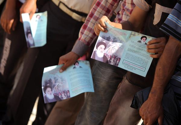 Shiite men who volunteered to join Iraq's security forces hold up pamphlets bearing images of Ayatollah al-Sistani as they queue at a recruitment center in Baghdad. The recruitment efforts of clerics in Najaf have influenced the ongoing struggle across Iraq.