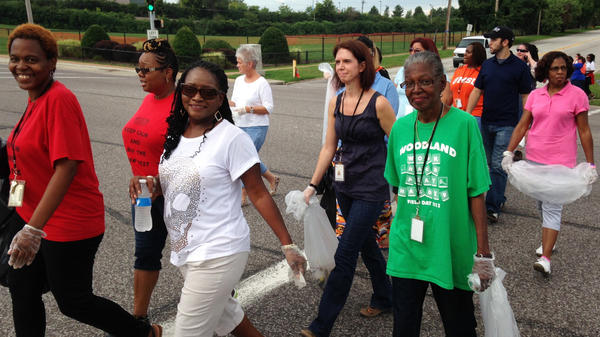 Teachers with the Jennings School District pick up trash Tuesday on West Florissant Avenue in Ferguson, Mo., the scene of nightly police clashes. Jennings and the neighboring Ferguson school district have canceled class due to ongoing unrest.