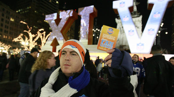 Super Bowl volunteer Ben Schreiber distributes fan guides for Super Bowl XLVI festivities in 2012.