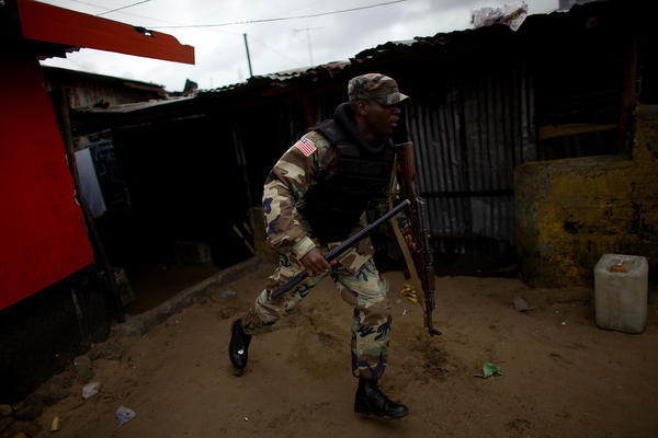 A soldier chases protesters through West Point after Liberia enforced a quarantine of the area.