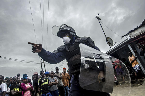 A riot policeman directs a crowd of protesters in the West Point neighborhood of Monrovia after a quarantine was enforced early Wednesday in an effort to contain the spread of Ebola.