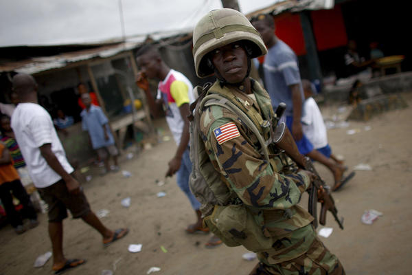 A police officer watches over residents of West Point during a riot after the area was subjected to a quarantine.